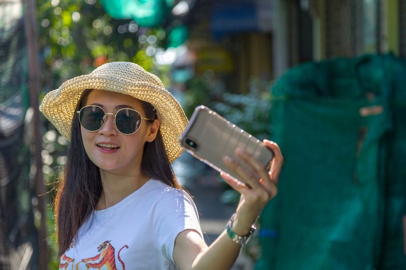She is take a photo Selfies Mobile Phone Wireless Technology Communication Smart Phone One Person Portable Information Device Portrait Sunglasses Lifestyles Technology Adult Smiling Leisure Activity Women Holding Photography Themes Happiness Outdoors