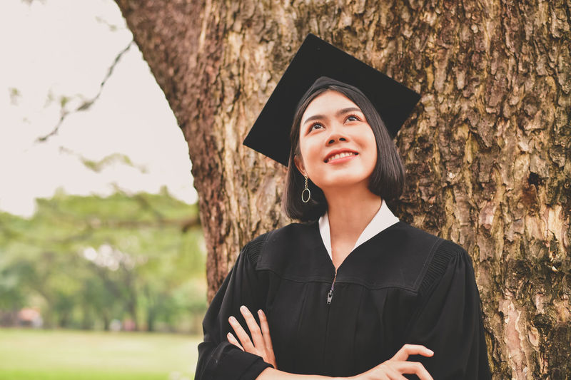 Thoughtful Young Woman In Graduation Gown With Arms Crossed Standing By Tree At Park