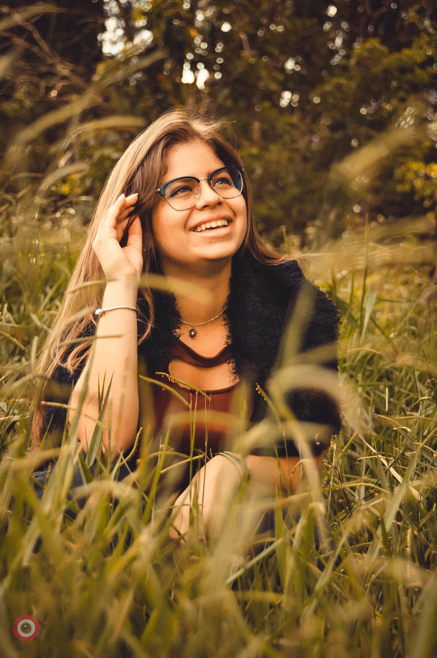 plant, one person, young adult, portrait, selective focus, smiling, young women, leisure activity, looking at camera, women, field, land, front view, adult, real people, beautiful woman, grass, nature, hair, outdoors, hairstyle