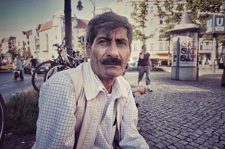 We met today in Hermannplatz, sitting next to each other; me staring at my phone, him observing the platz. Then we had a lovely yet chaotic chat. He has been in Germany for 8 months now and doesn't know if his family will be able to join. His German is very bad, he says, and language is everything here. Still, he was smiling most of the time and that is universal. Berlin City City Life City Street Focus On Foreground Hermannplatz Natural Light Portrait Portrait Portraits Real People Refugeeswelcome Street Photography The Portraitist - 2017 EyeEm Awards The Street Photographer - 2017 EyeEm Awards