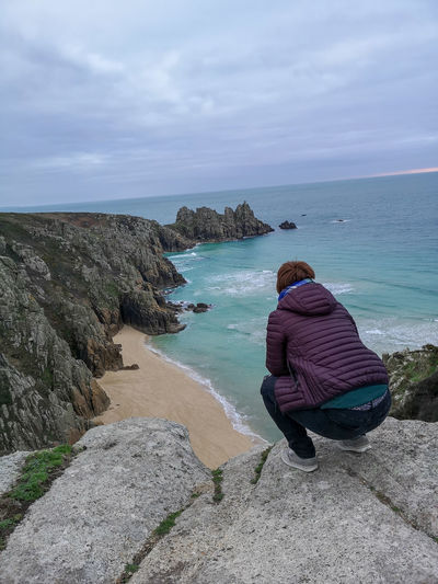 admiring what's on your doorstep EyeEm Nature Lover Woman Crouched Down Looking At The View Cornwall Uk Logan Rock Blue Sea And Clear Water Eyeemphotography Water Sea Beach Sand Wave Women Rear View Sky Horizon Over Water Shore Rocky Coastline Hiker Sandy Beach Seaside Ocean