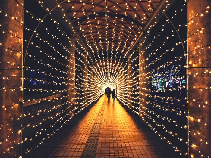 Illuminated christmas decorations at covered walkway
