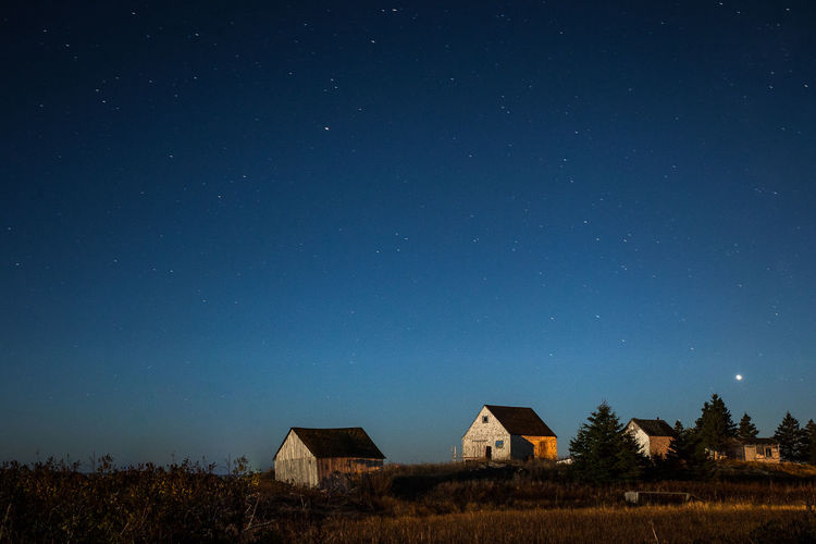 Houses On Field Against Sky At Night