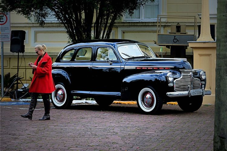 The red coat and the black car! 40's Style Black Car Casual Clothing City City Life Coat Day Fine Art Photography Lady Lifestyles Old Car Outdoors Red Coat Street Photography Vintage Winter Coat Woman