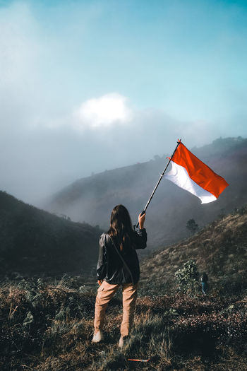 Woman standing with flag on field against mountains
