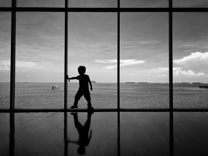 Silhouette Boy Looking At Sea Against Sky Through Window