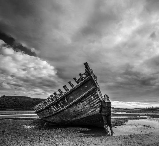 Woman standing by shipwreck at beach against cloudy sky