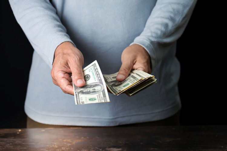 Midsection of man giving money at table