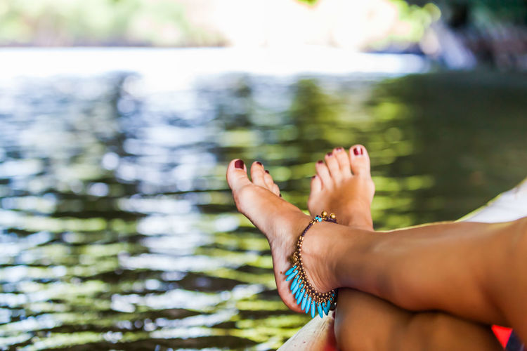 Low section of woman sitting at lake