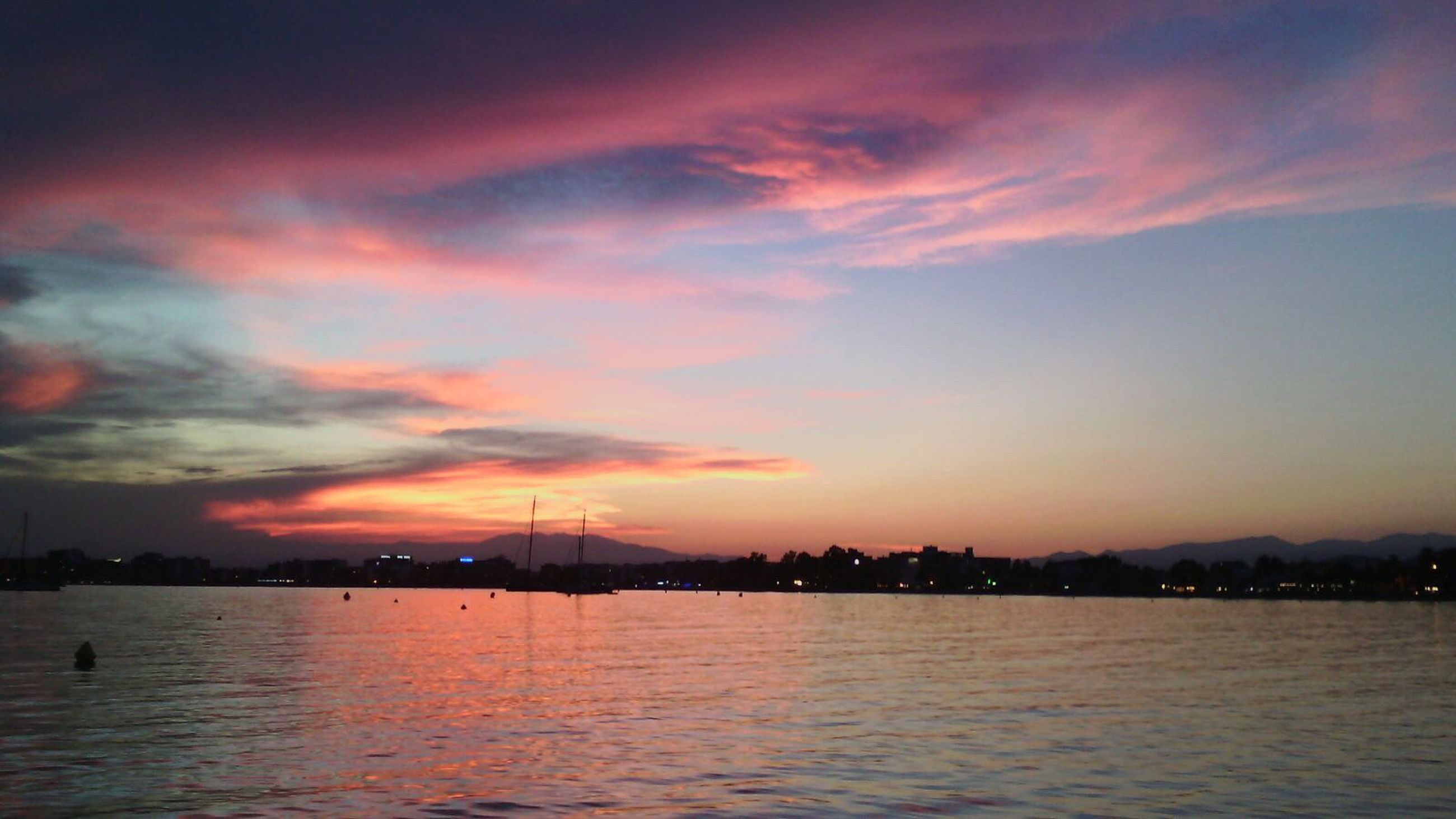 sunset, water, waterfront, sky, orange color, scenics, sea, illuminated, silhouette, tranquil scene, beauty in nature, tranquility, cloud - sky, reflection, building exterior, architecture, river, built structure, dusk, nature