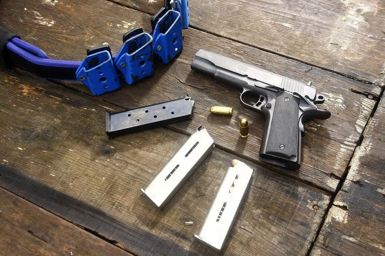 High Angle View Of Handguns On Wooden Table