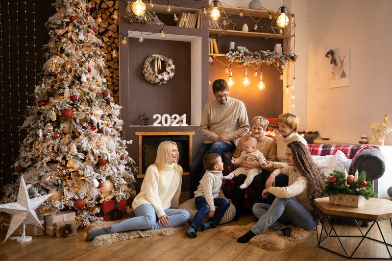 Cheerful family sitting at home by christmas tree