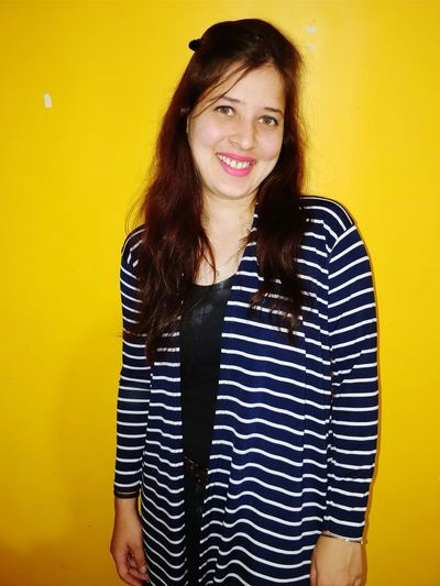 Portrait Of Smiling Young Woman Against Yellow Wall