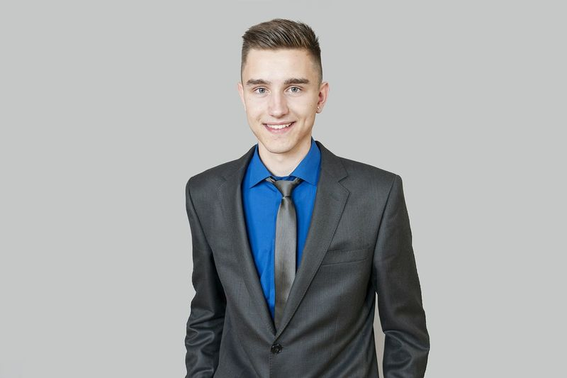 Portrait of young smiling businessman wearing suit while standing against gray background