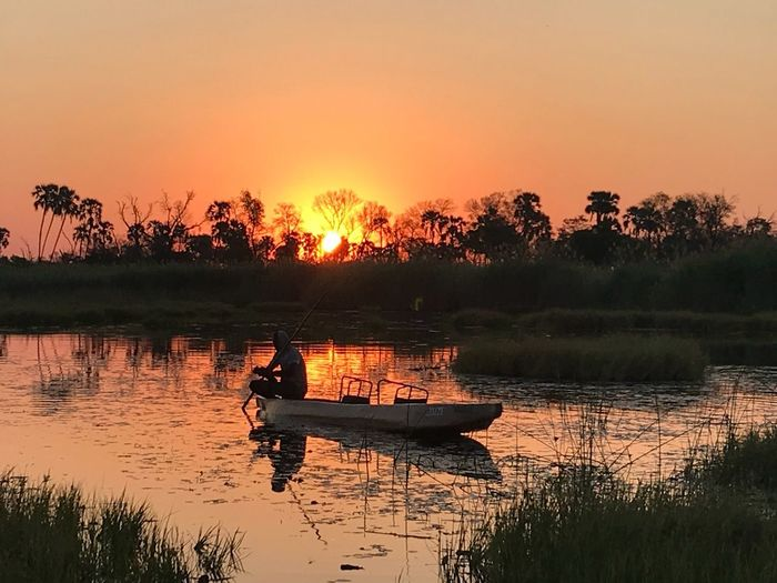 Sunset in the Okavango Delta EyeEm Selects Sunset Sky Water Tree Reflection Beauty In Nature Lake Scenics - Nature Orange Color Mode Of Transportation Nature Nautical Vessel Silhouette Transportation Tranquility