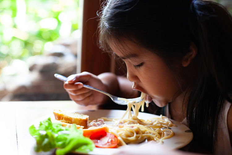 Girl having pasta at table
