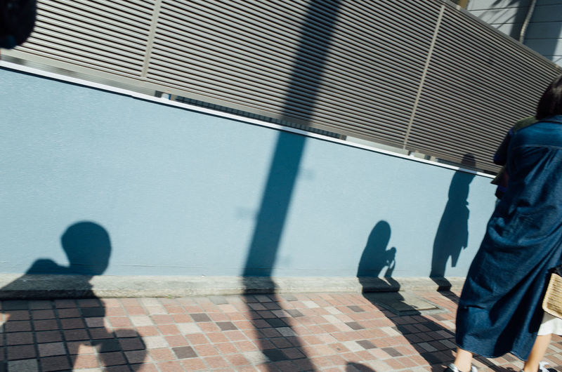 Close-up of woman and several silhouette of kids against street wall in tokyo japan