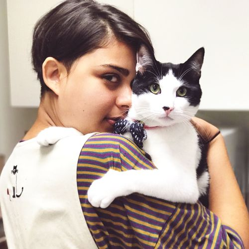 Portrait Of Young Woman With Cat At Home