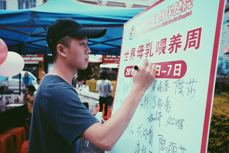 Side view of young man standing by text