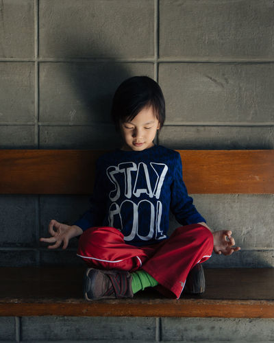Front View Of A Cute Boy Doing Yoga On A Bench