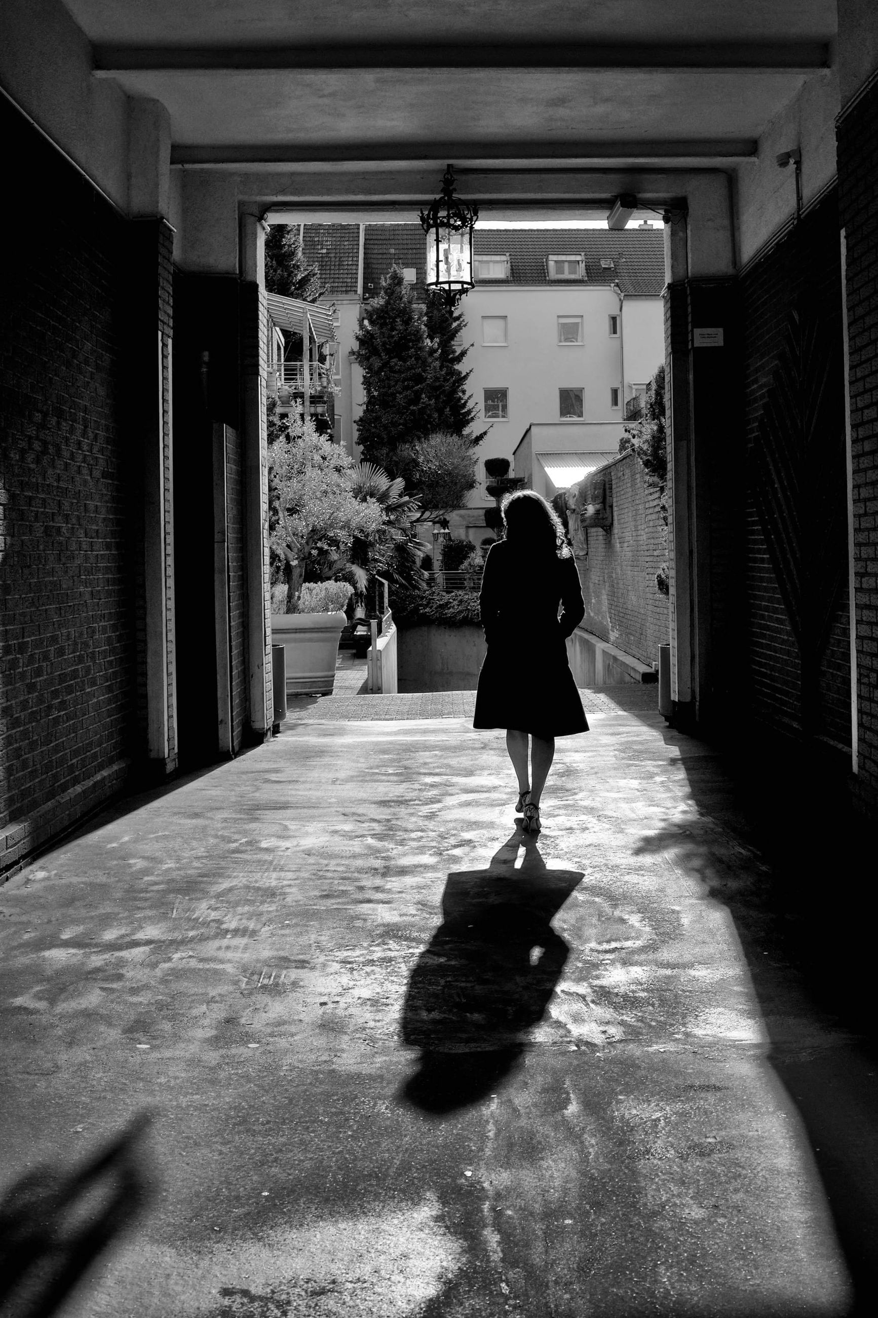 black, white, full length, one person, darkness, architecture, walking, rear view, black and white, built structure, road, light, adult, monochrome, women, shadow, snapshot, monochrome photography, street, lifestyles, building exterior, leisure activity, sunlight, day, city, standing, footpath, infrastructure, building, nature, outdoors, casual clothing, person