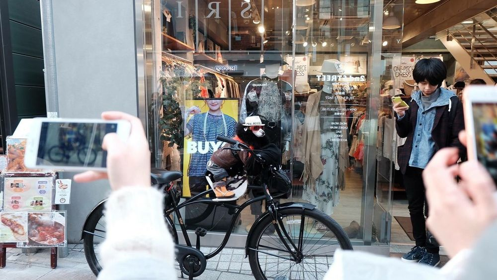 Mobile Conversations Bicycle Retail  Men Adults Only Consumerism Bicycle Shop Technology Choice Store Occupation Business Finance And Industry Adult Outdoors People Real People Only Men Young Adult One Person Human Hand Day