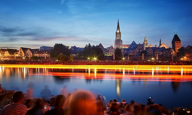 Photo of the Light Serenade in Ulm, Germany ( Lichterserenade). On this Event, many Candles flow down the Danube River creating a really Romantic mood. Both margins of the Danube river are completely full. Cities At Night
