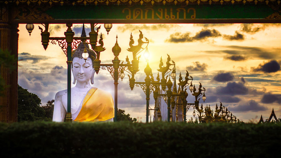 Panoramic view of statue against sky during sunset