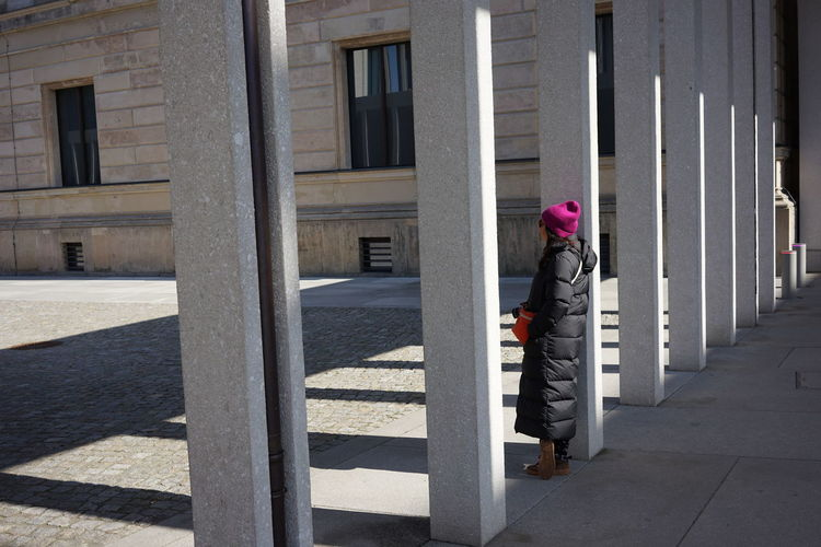 Woman walking by building in city