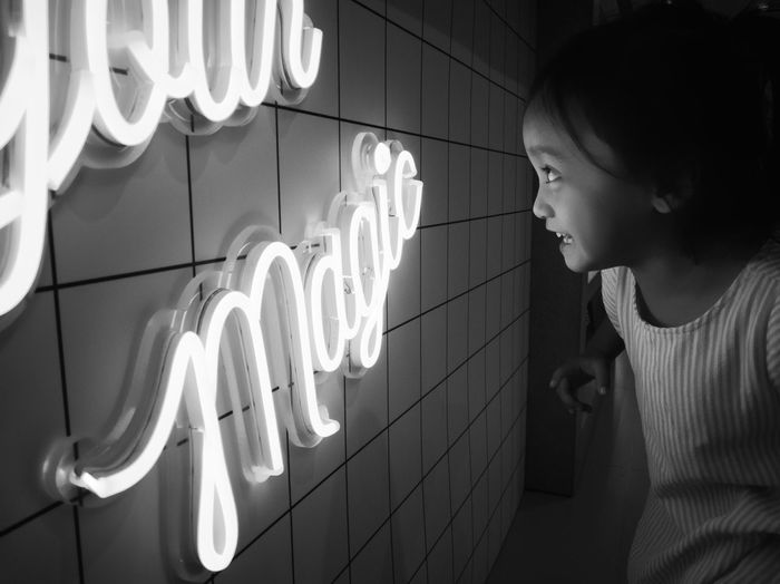 Smiling girl looking at illuminated text on wall
