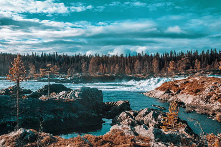 Panoramic view of rocks on shore against sky