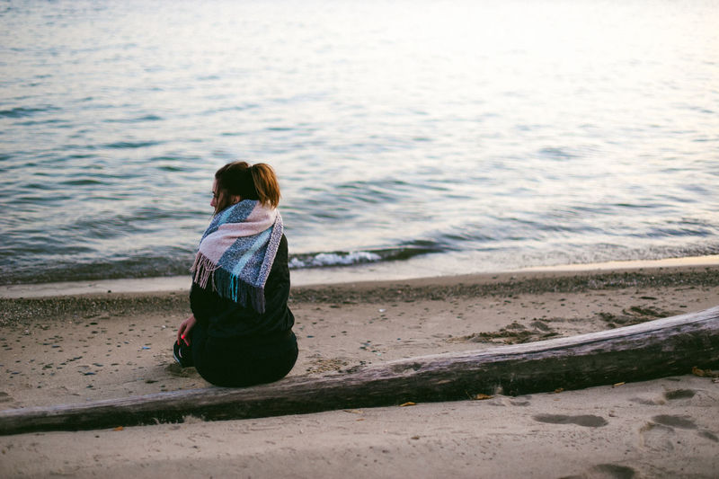 Rear view of woman sitting at beach during sunset