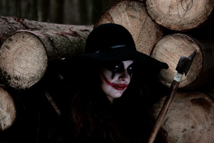 Portrait Of Woman In Zombie Make-Up With Axe Against Logs