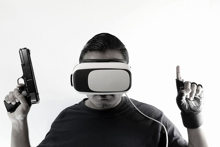 Young man with virtual reality headset holding gun wearing gloves and hands in the air looking straight Console Display Futuristic Gamer Gaming Glasses Gloves Goggles Gun Headset Innovation New Pistol Playing Riffle Role Playing Game Shooter Shooting Technology Virtual Virtual Reality War Weapon White Background Wireless Technology
