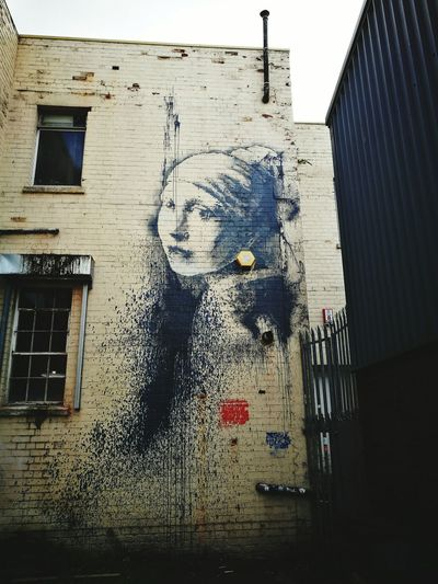 Banksy The Girl With The Pierced Eardrum Architecture Building Exterior Banksyart built structure outdoors graffiti day banksy Window No People Sky