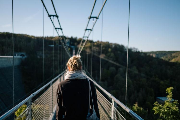 Rear view of woman on footbridge against sky
