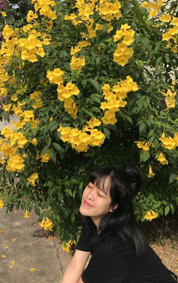 Young woman standing by yellow flowering plants