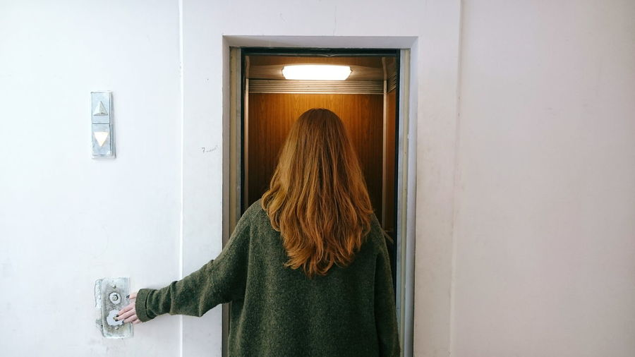 Rear view of woman against elevator in building