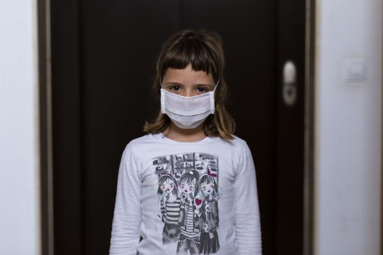 Portrait of girl standing against door