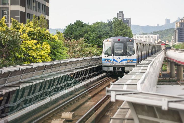 Train by railroad tracks in city