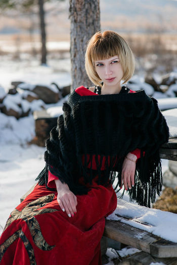 Young Woman Sitting On Bench During Winter