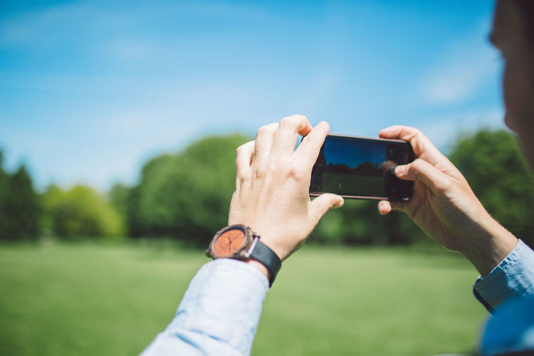 Cropped Hands Of Man Photographing Green Landscape Through Mobile Phone During Sunny Day