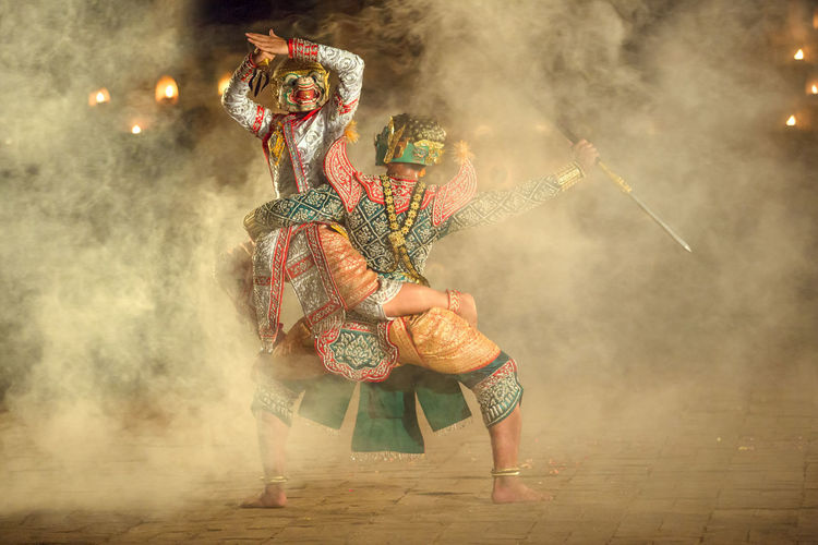 People Dancing In Traditional Clothing At Night