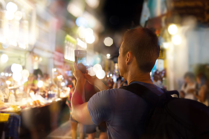 Man photographing while standing on street in illuminated city at night