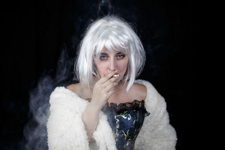 Portrait Of Female Model Smoking Cigarette Against Black Background