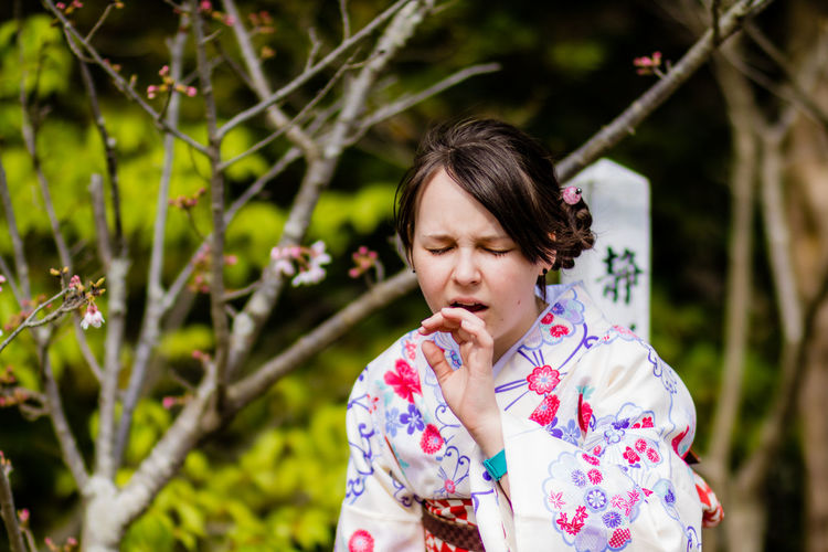 Woman In Kimono Making Face Against Trees