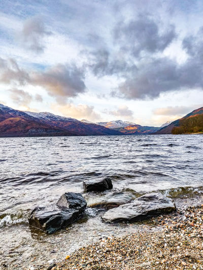 My first visit at Loch Lomond lake! :) Water Cloud - Sky Beauty In Nature Scenics - Nature Sky Mountain Tranquility Tranquil Scene Nature No People Rock Solid Day Rock - Object Non-urban Scene Land Sea Mountain Range Idyllic Outdoors Flowing Water Scotland Phone Photography Oneplus