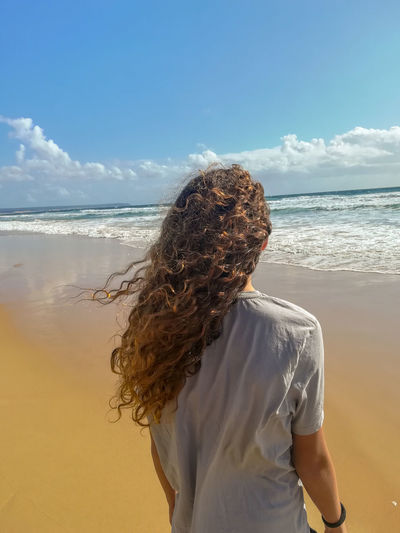 Rear view of girl with curly hair standing on beach