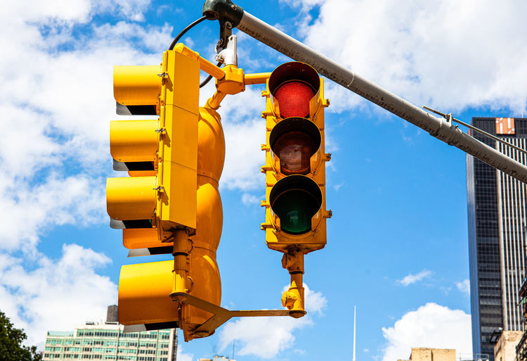 Low angle view of yellow road signal against sky