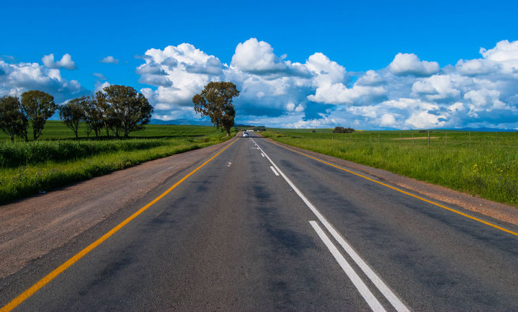Beauty In Nature Cloud - Sky Diminishing Perspective Direction Dividing Line Environment Land Landscape Long Marking Nature No People Outdoors Road Road Marking Scenics - Nature Sign Sky Symbol The Way Forward Tranquil Scene Transportation vanishing point